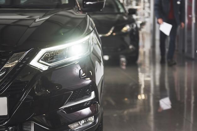 Os faróis e o capô de um carro preto de luxo.