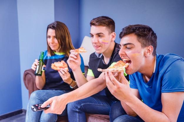 Os fãs de futebol no sofá comendo pizza