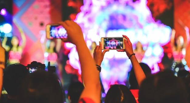 Os fãs estão se divertindo, tanto tirando fotos com a câmera quanto com o celular. intérprete de concerto