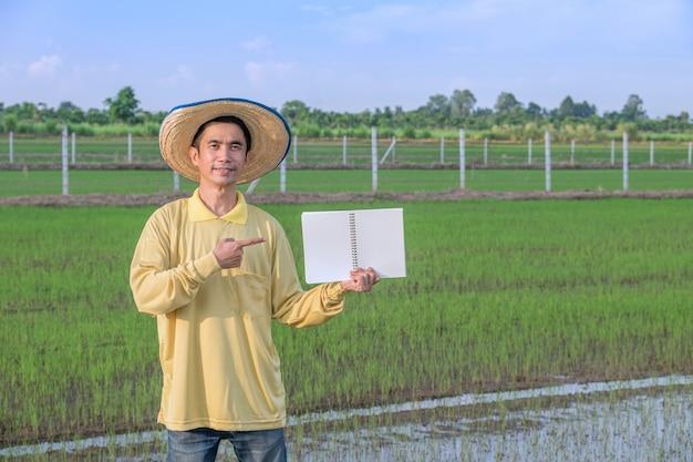 Os fazendeiros asiáticos usam amarelo em pé e segurando o caderno na fazenda verde. imagem para apresentação.