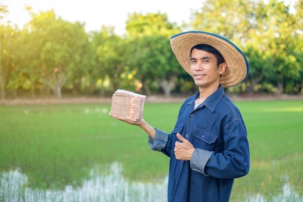 Os fazendeiros asiáticos usam camisas de fantasias tradicionais segurando dinheiro das notas tailandesas na fazenda verde. imagem para apresentação.