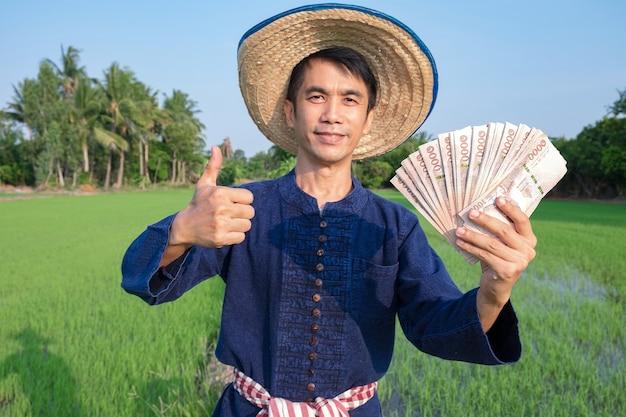 Os fazendeiros asiáticos usam camisas de fantasias tradicionais segurando dinheiro das notas tailandesas na fazenda verde.