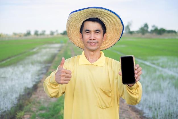 Os fazendeiros asiáticos usam camisetas amarelas segurando o smartphone e o polegar para cima na fazenda verde.