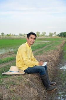 Os fazendeiros asiáticos usam camisetas amarelas sentados e escrevendo cadernos na fazenda verde.
