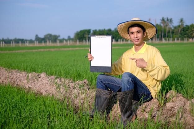 Os fazendeiros asiáticos usam camisetas amarelas sentados e mostram um tabuleiro de papel na fazenda verde. imagem para apresentação.