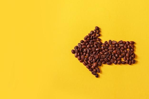 Os feijões de café deram forma no formulário da seta isolado no fundo amarelo.