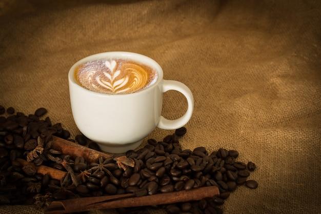 Os feijões de café e o café da xícara no saco de pano selecionam o foco, tom da cor do vintage ou tom escuro