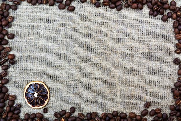 Os feijões de café encontram-se em uma serapilheira de pano de linho. fundo retrô