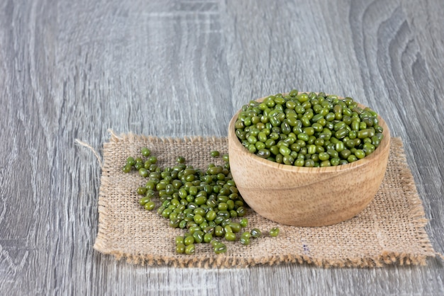 Os feijões verdes transbordam bacias de madeira e empilham-se no saco tecido