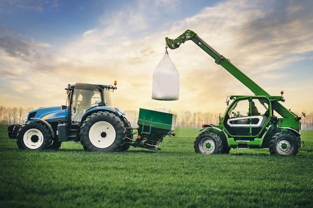 Os fertilizantes são transportados em sacos no reboque do trator no campo na primavera