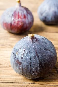 Os figos são maduros frescos em uma superfície velha de madeira.
