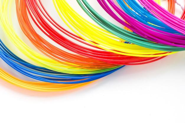 Os filamentos plásticos do arco-íris colorido para 3d encerram a colocação no fundo branco. novo brinquedo para criança.