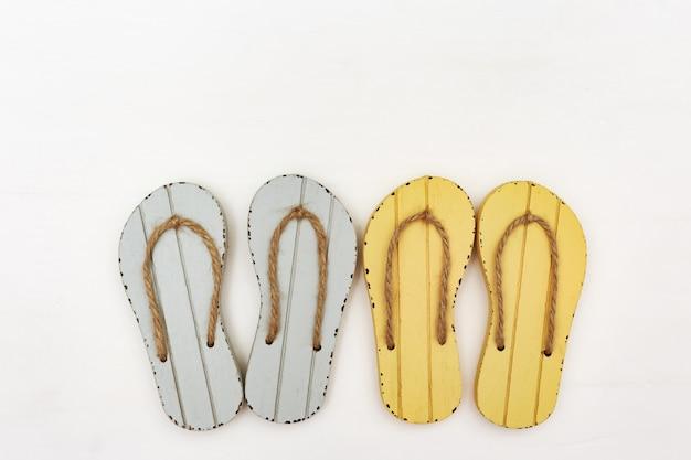Os flip-flops cinzentos e amarelos fecham-se acima no fundo branco. sapatos de verão em fundo branco.