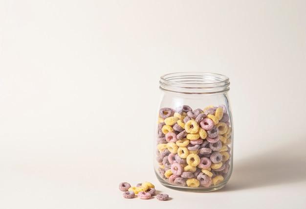 Os flocos de milho coloridos doces soam em uma jarra de vidro em um fundo amarelo. vista frontal e imagem do espaço de cópia