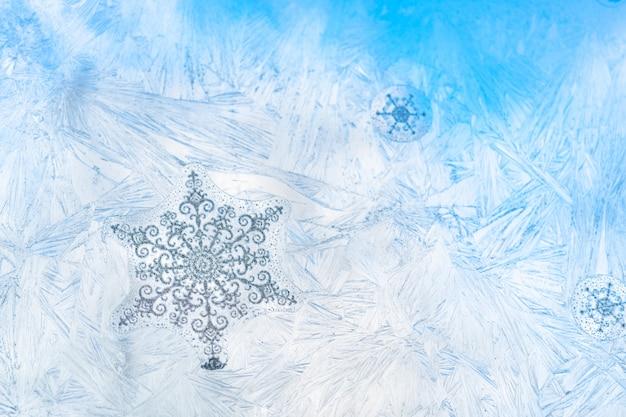 Os flocos de neve da etiqueta no vidro de janela geado gelo com o céu azul visto no fundo