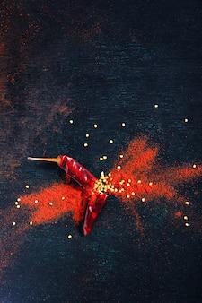 Os flocos de pimenta vermelha e o pó de pimentão estouraram no fundo preto