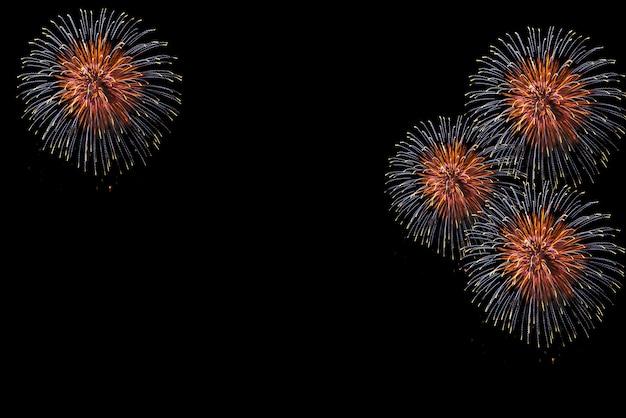 Os fogos-de-artifício coloridos bonitos indicam para a celebração no fundo preto.