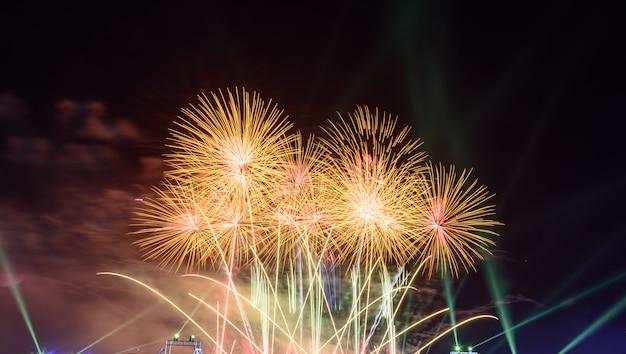 Os fogos-de-artifício coloridos na noite iluminam acima o céu com exposição do brilho.