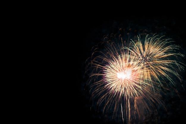Os fogos-de-artifício indicam para a celebração no fundo preto. conceito de feriado de ano novo.