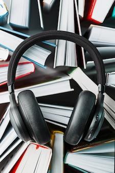Os fones de ouvido pretos sem fio estão nos livros. o conceito de aprendizagem através de um audiolivro. para ouvir o livro.
