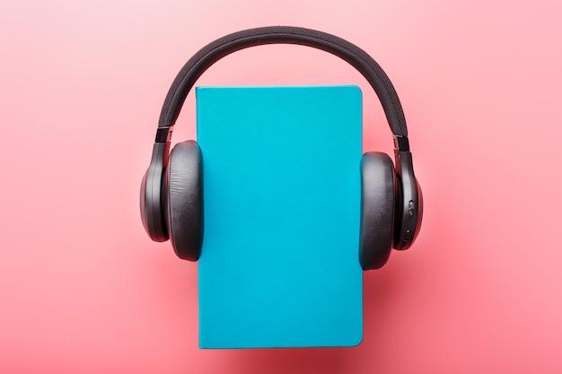 Os fones de ouvido são usados em um livro de capa dura azul sobre um fundo rosa, vista superior.