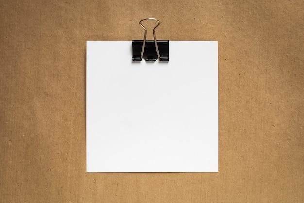 Os formulários brancos são combinados por um clipe de papel preto sobre um fundo de papel kraft. vista do topo. copie o espaço