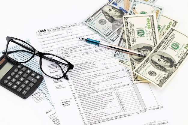 Os formulários fiscais com os óculos, o dinheiro e a caneta.