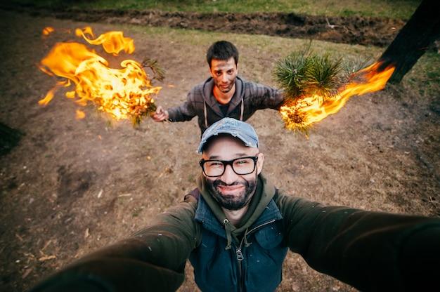 Os frineds fazem selfie. garotos engraçados loucos mexem. homens na natureza brincando e brincando com fogo. excêntricos bizarros estranhos jovens incomuns com caras sujas festa louca na floresta. queime, chamas, fume.