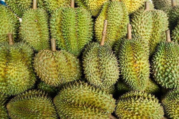 Os frutos do durian arranjam junto para a venda introduzir no mercado em tailândia.