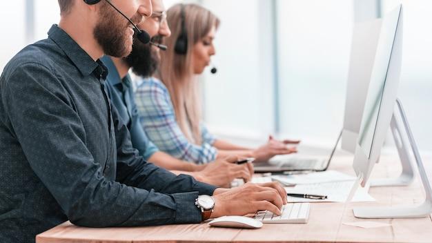 Os funcionários do call center trabalham em computadores modernos