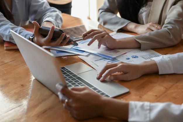 Os funcionários usam o laptop para trabalhar na mesa.