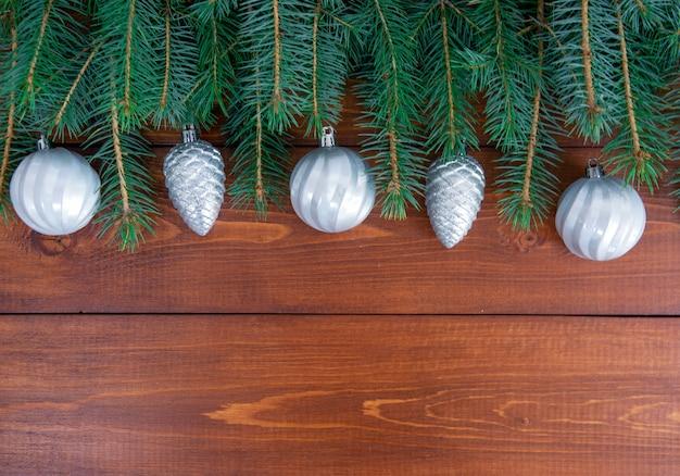 Os galhos da árvore de natal com a decoração nas tábuas de madeira escura