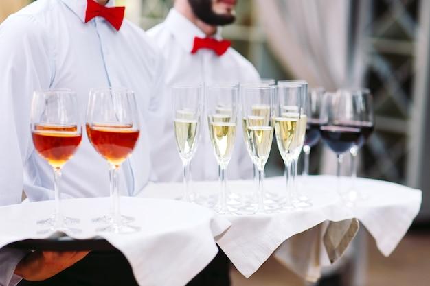 Os garçons cumprimentam os hóspedes com bebidas alcoólicas. champanhe, vinho tinto, vinho branco nas bandejas.