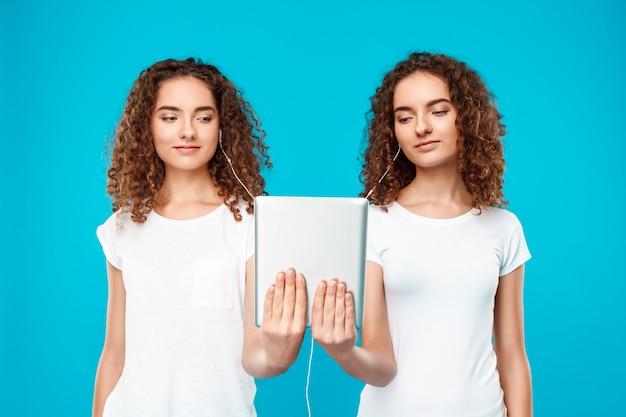 Os gêmeos de duas mulheres que olham a tabuleta, sorrindo sobre o azul.