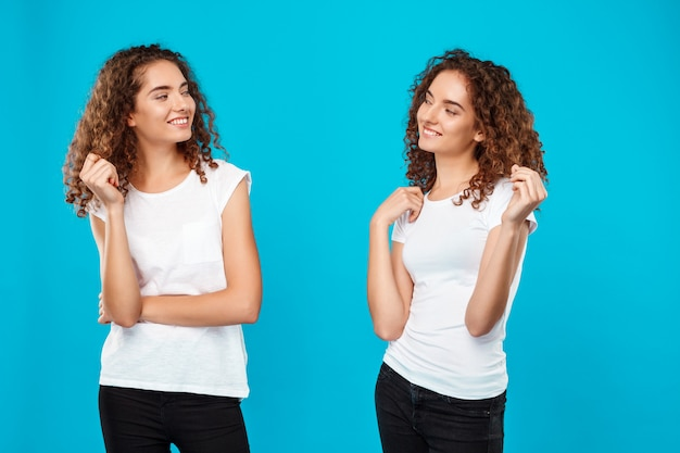 Os gêmeos de duas mulheres que olham se sobre o azul.