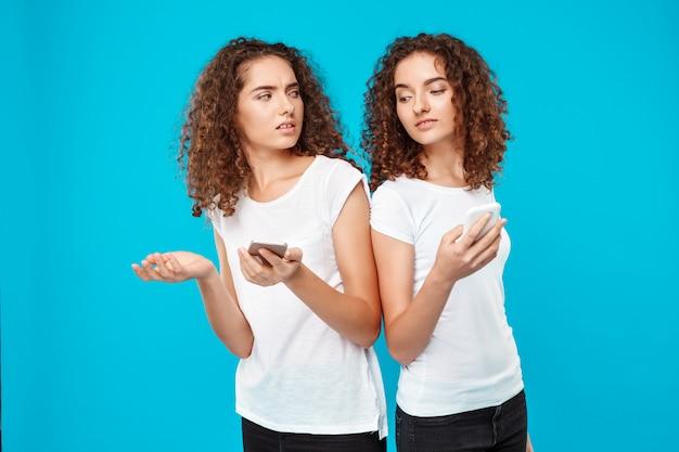Os gêmeos de duas mulheres que olham telefones sobre o azul.