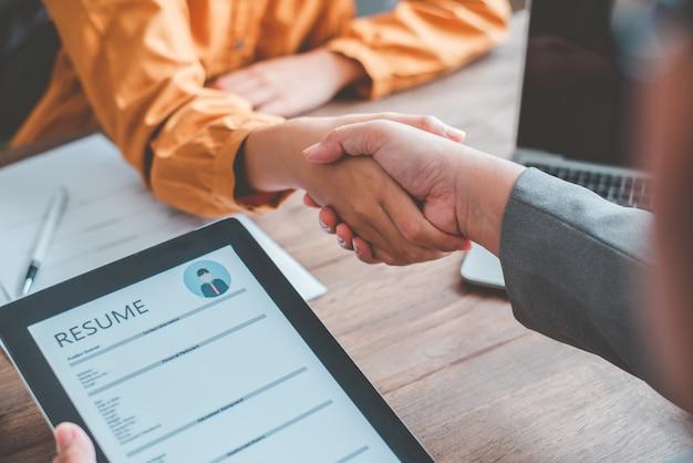 Os gerentes de rh dão as mãos aos candidatos a empregos, aceitam propostas e concordam em trabalhar juntos na empresa.