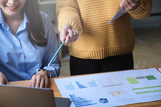 Os gestores de fundos consultam a equipe e discutem sobre a análise do mercado de ações de investimento por relatório financeiro.