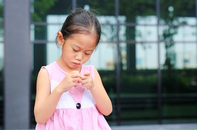 Os gestos de crianças que não têm confiança. garota de criança pretende os dedos dela.