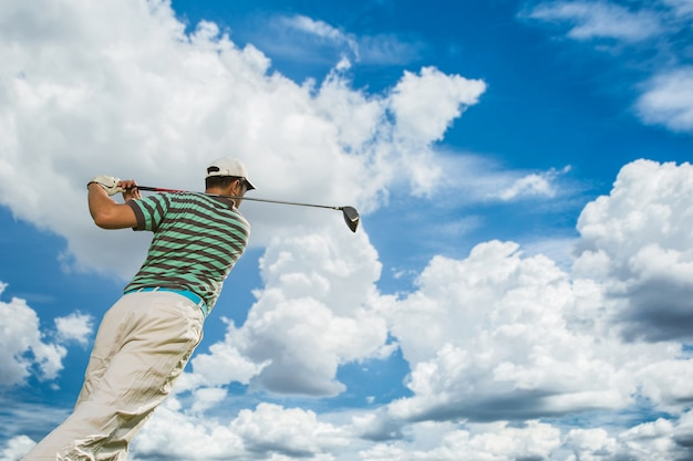 Os golfistas vão tee bata a bola de golfe com a força em um dia claro