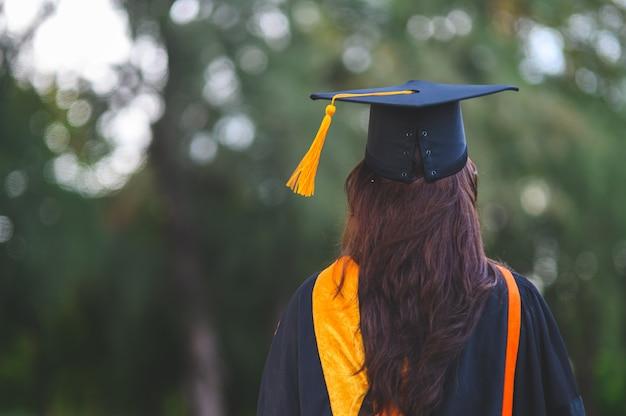 Os graduados usam vestido preto acadêmico no dia da formatura na universidade