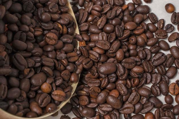 Os grãos de café caem de um close-up de um recipiente de madeira
