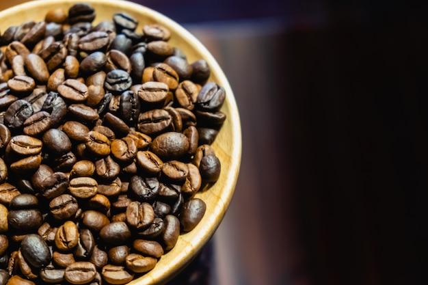 Os grãos de café em prato de madeira