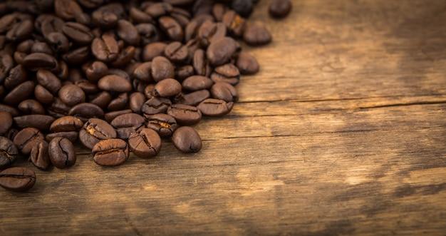 Os grãos de café em uma tabela de madeira