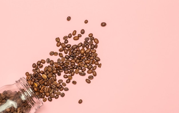 Os grãos de café estão espalhados em um fundo rosa. conceito café