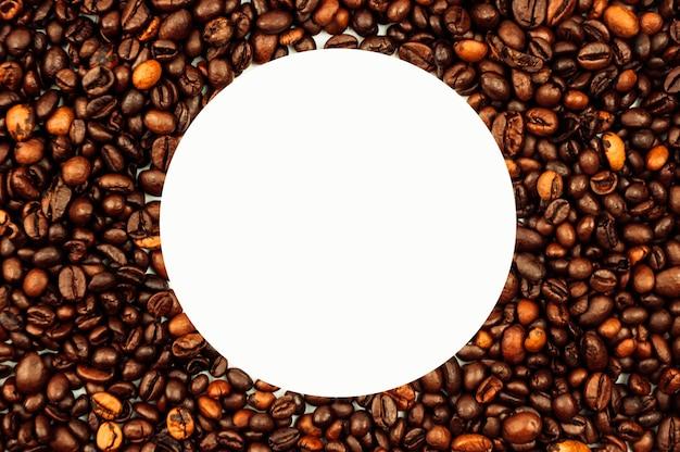 Os grãos de café estão espalhados pela superfície em um fundo branco e vazio. um punhado de grãos de café marrons. fundo de café com espaço de cópia para uma inscrição