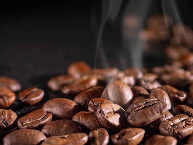 Os grãos de café fecham-se em um fundo preto brilhante.
