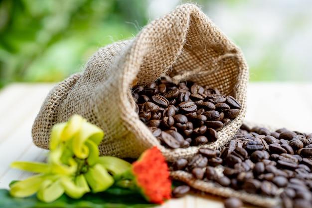 Os grãos de café saem do saco no chão de madeira na manhã.