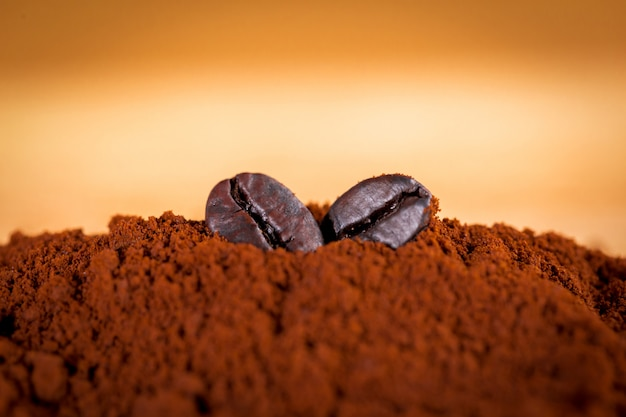 Os grãos de café são colocados em pó de café. filtre fotos em estilo vintage.