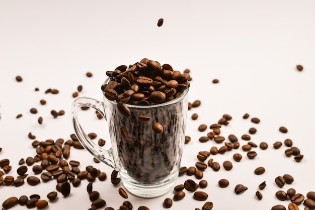 Os grãos de café são colocados em uma xícara de vidro em uma superfície branca